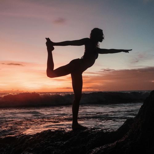 Frau Silhouette Yoga Yogagurt Yogaübungen am Strand vor Sonnenuntergang