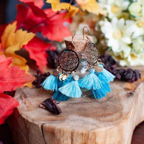 Boho ohrringe blau mit quasten golf auf Holz mit herbstlichen Blättern